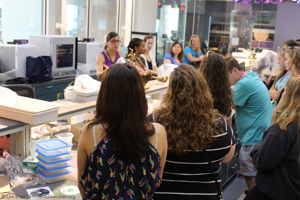North Carolina Governor's School students look on as Students Discover teachers and scientists discuss ant behavior at the North Carolina Museum of Natural Sciences. They are standing in a lab with glass walls.